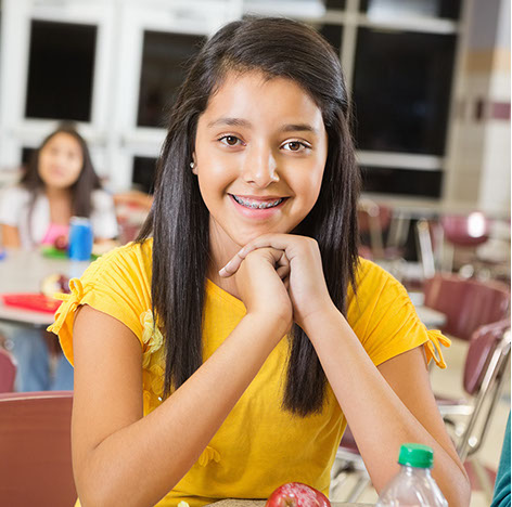 Girl smiling with braces sitting in a lunch room.